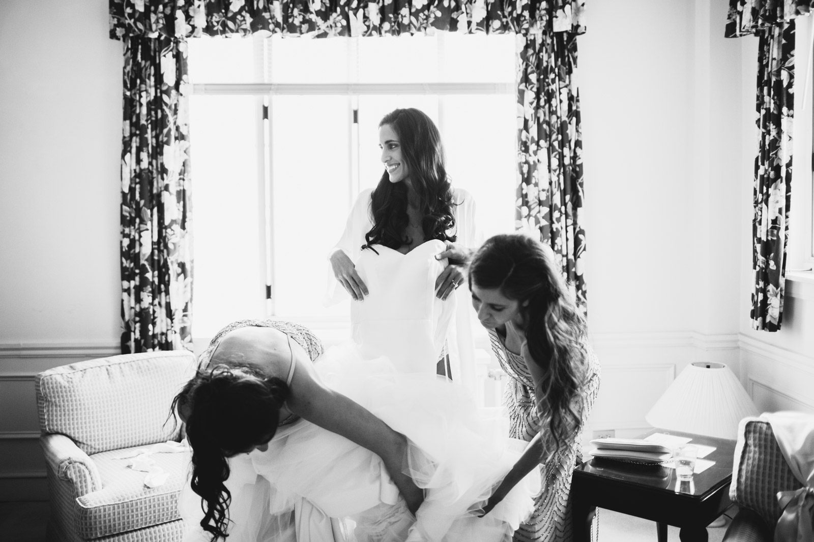 photo of the bride putting on her dress at homestead hotel in Evanston captured by Mark Trela Photography