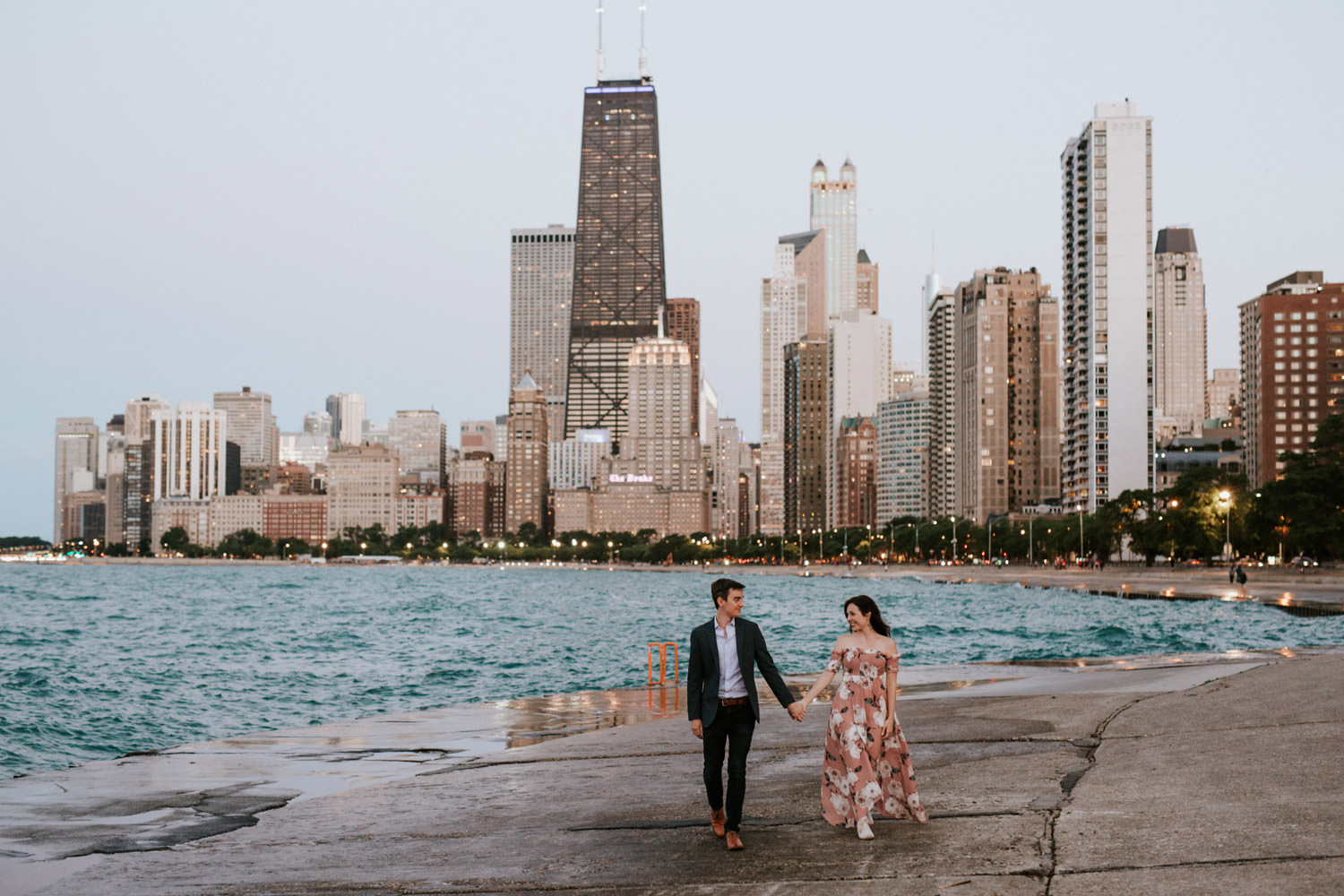 Couple waling down the lake front at north Avenue beach, picture taken during their engagement session
