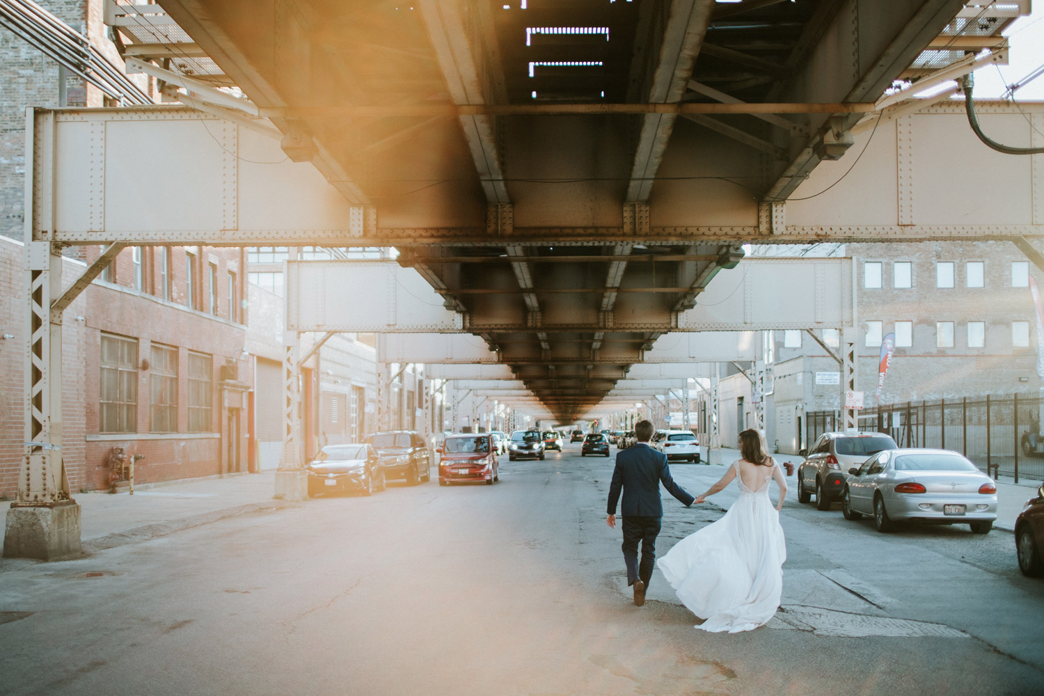 Bride and groom walking under train tracks in Chicago