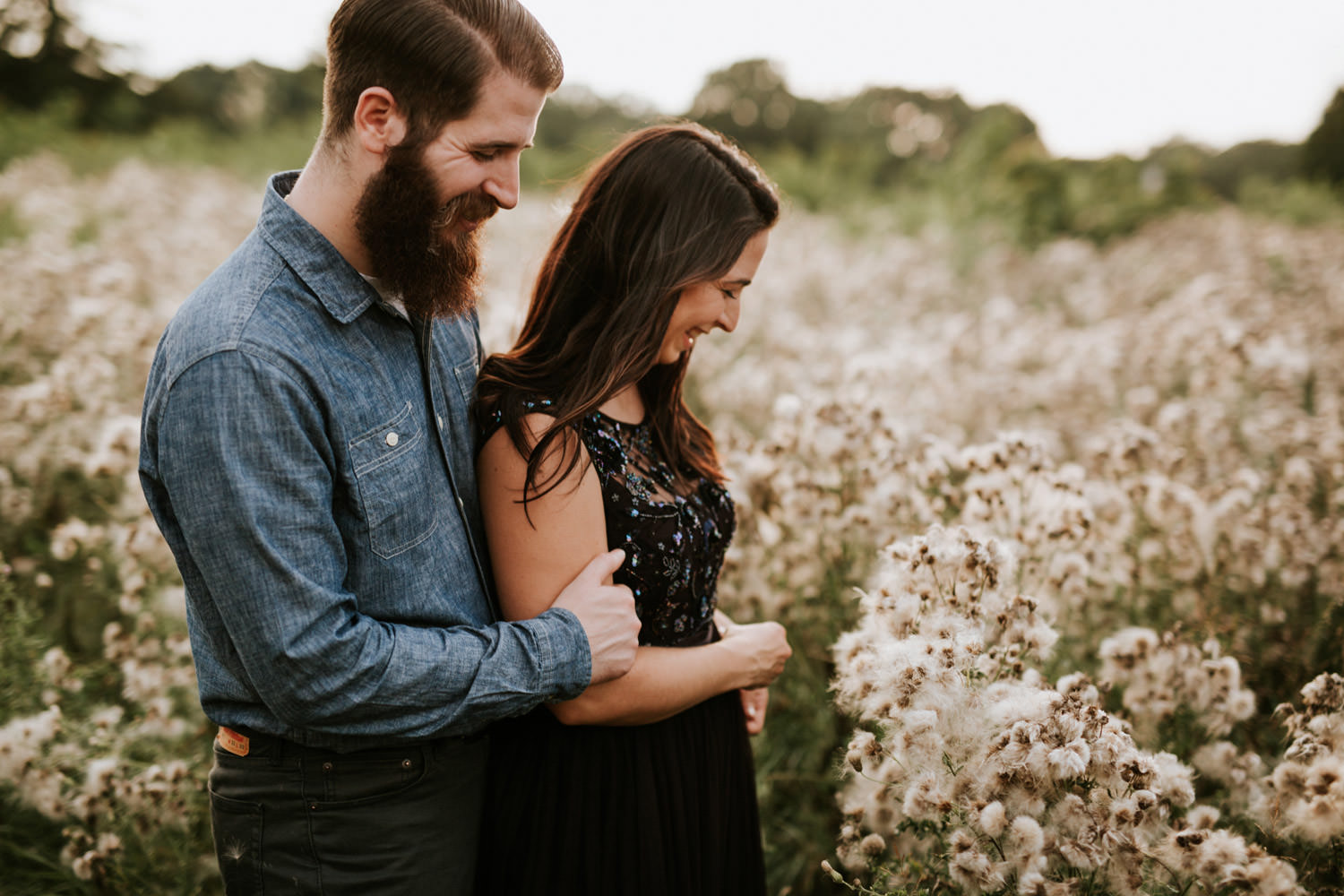 two lovers walk through native grass and plants during their engagement session at St. James Farm
