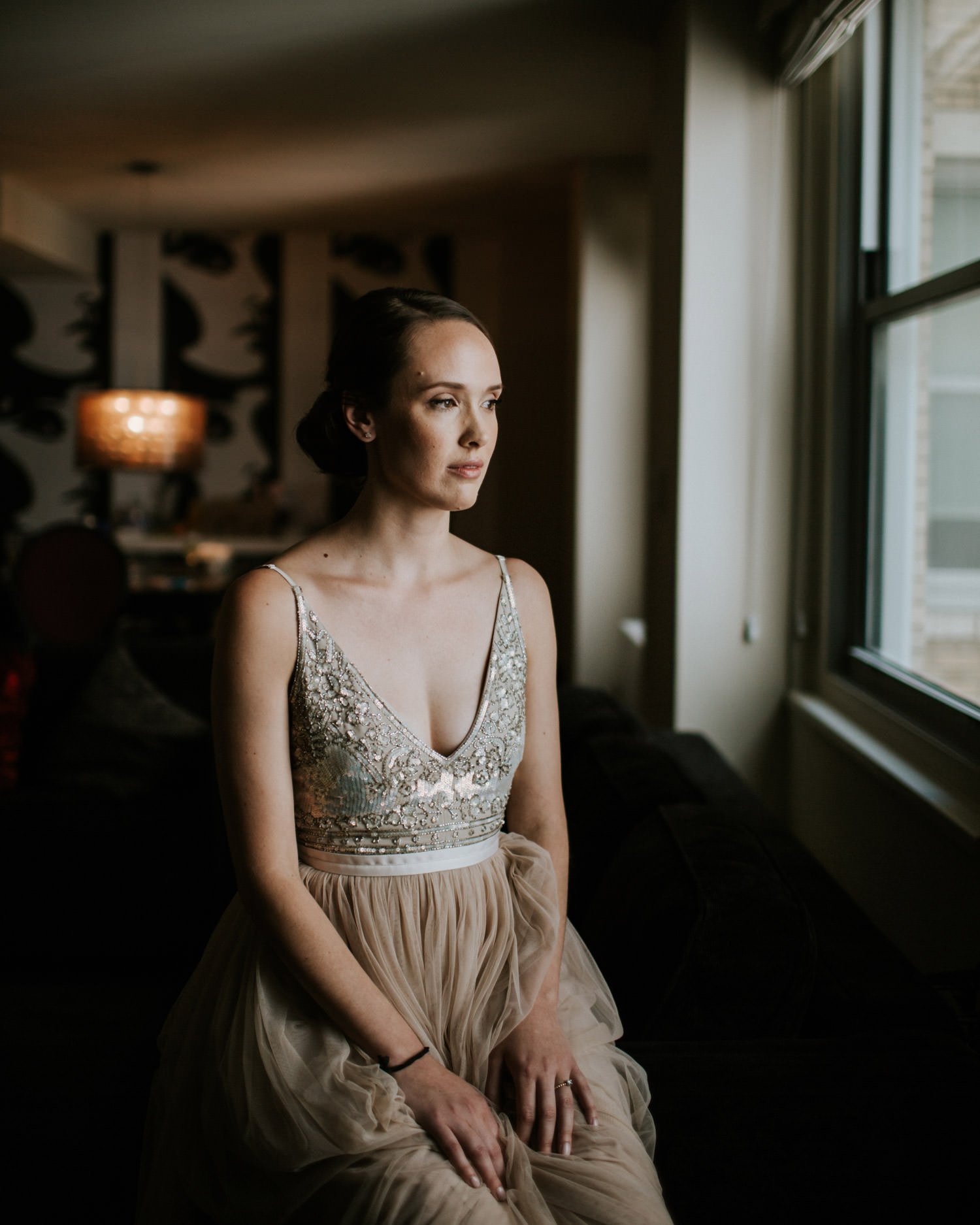 Bride in her BHLDN dress photographed by the window in Chicago hotel, moments before the first look