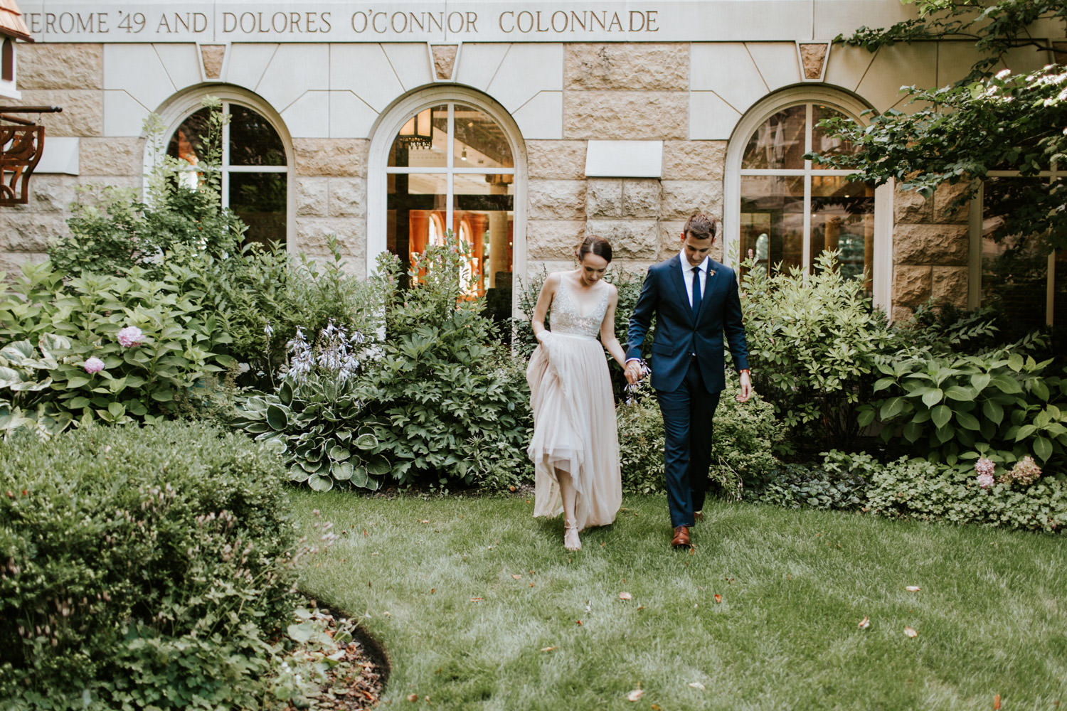 Bride and groom walk together after seeing each other for the first time. Photographed by Mark Trela at Saint Ignatius College in Chicago