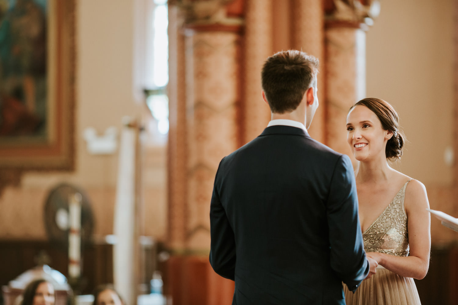 Groom puts the ring on the bride's finger at Holy Family Catholic Church