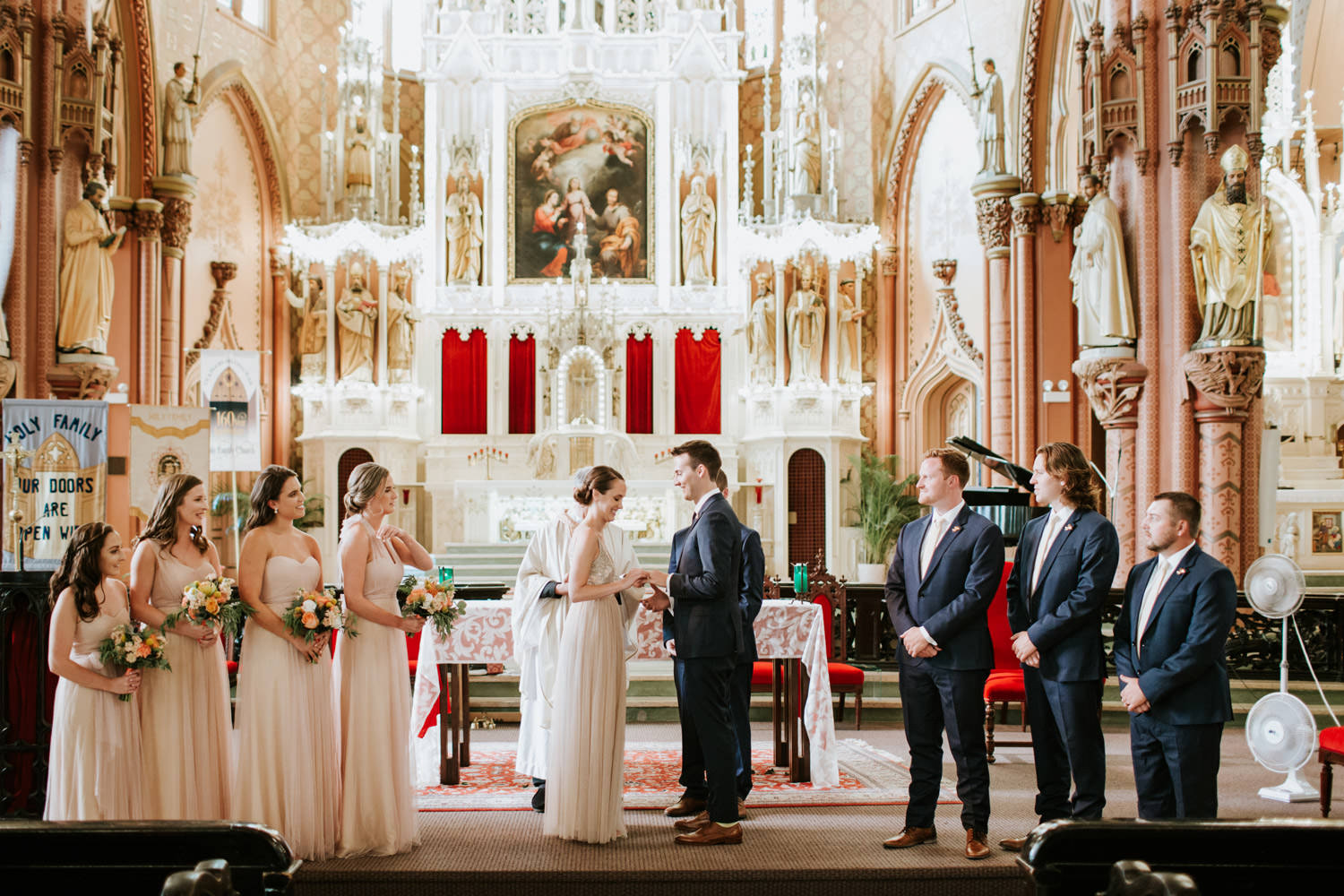 Bride and groom exchange vows during the wedding at Holy Family Catholic Church in Chicago