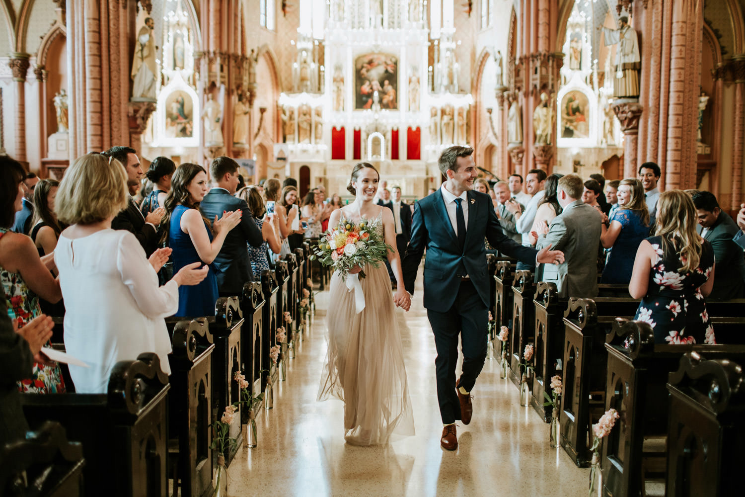Bride and groom walk out the church after the wedding ceremony at Holy Family Catholic Church