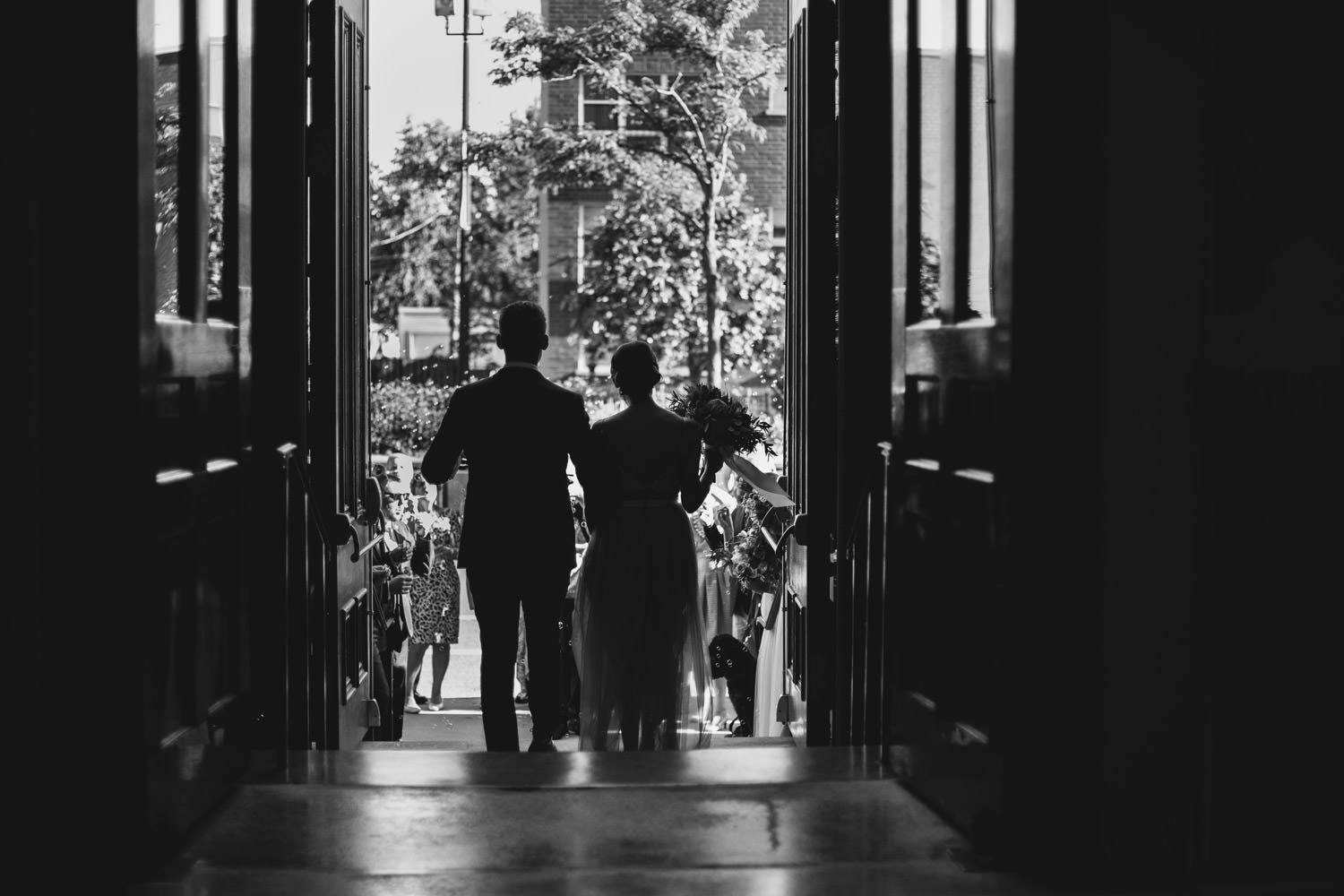 Black and white image of bride and groom walking out of the Holy Family Catholic Church after the wedding ceremony