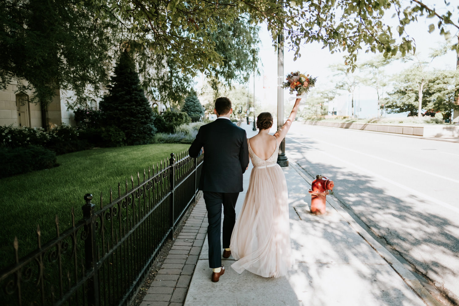 Bride and groom walk down the street in Pilsen, Chicago
