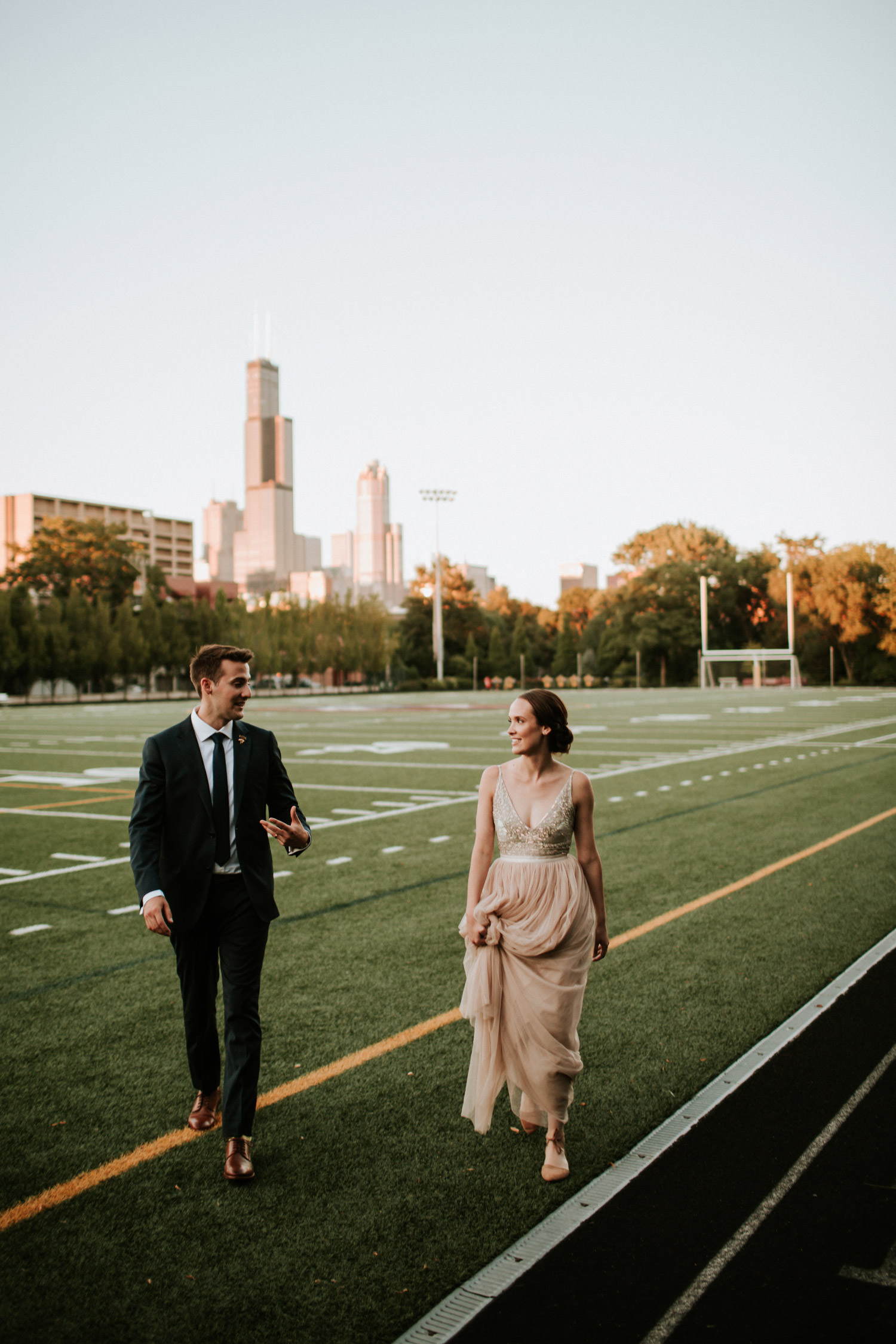 Bride and groom walk on the football field in Chicago