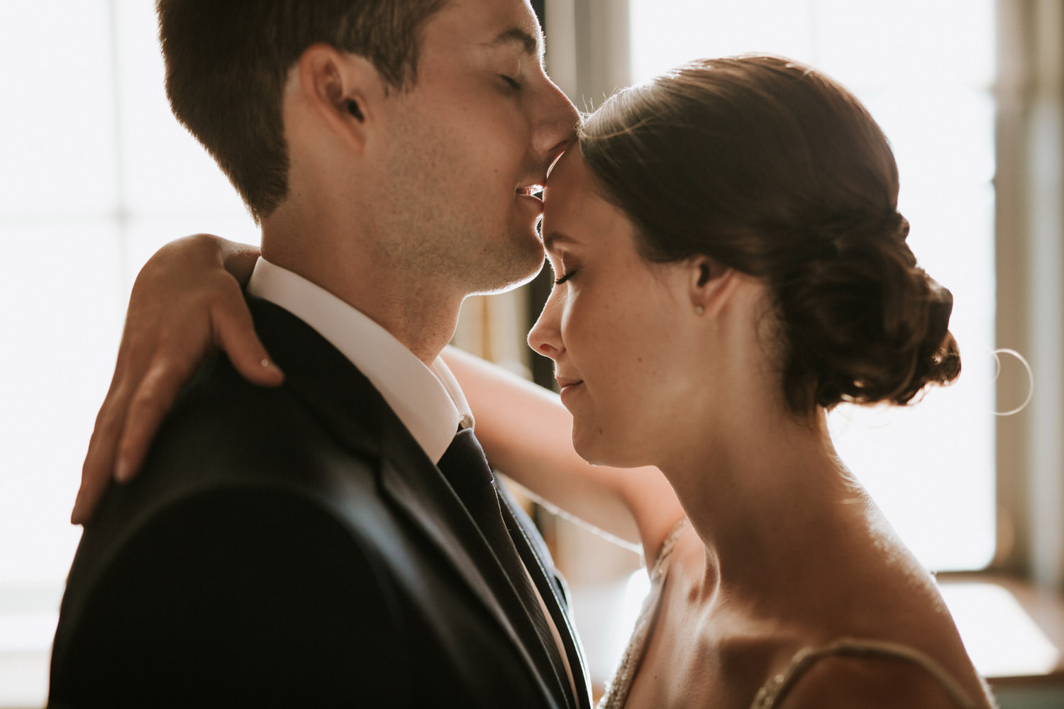 Groom kisses her bride at Saint Ignatius College Prep