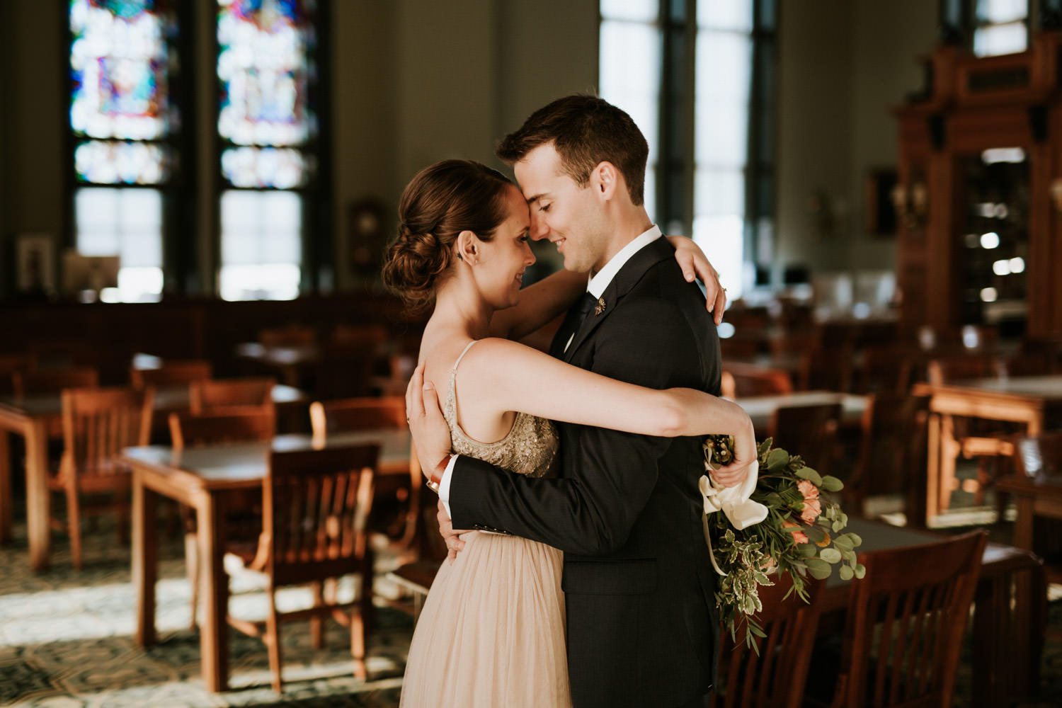 Bride and groom embrace in library of Saint Ignatius College at Chicago