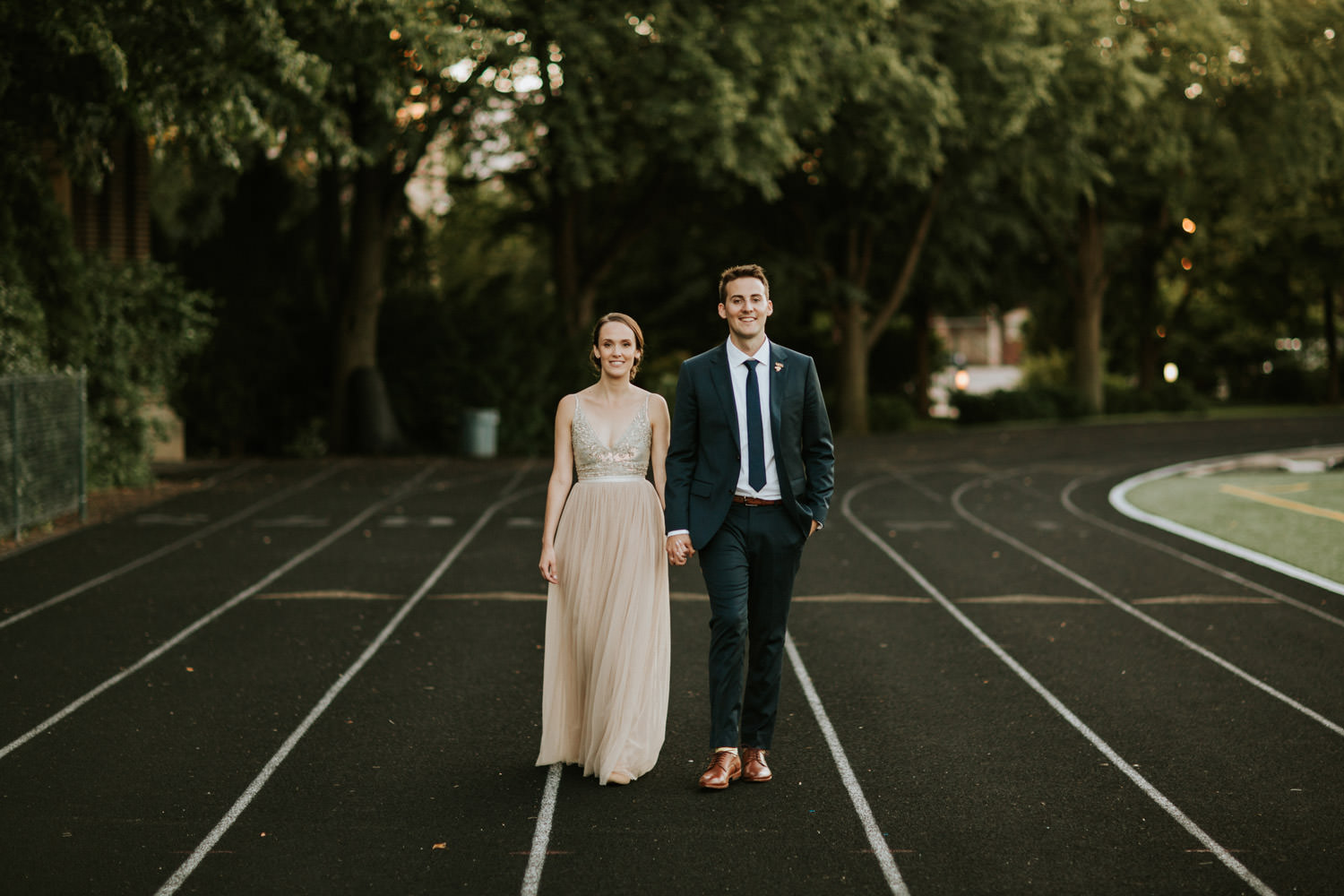 Portrait of a bride and groom walk on a track field in Chicago