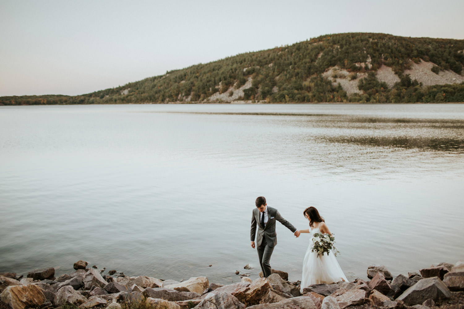 bride and groom walk along the lake at devil's lake state park in winsconsin