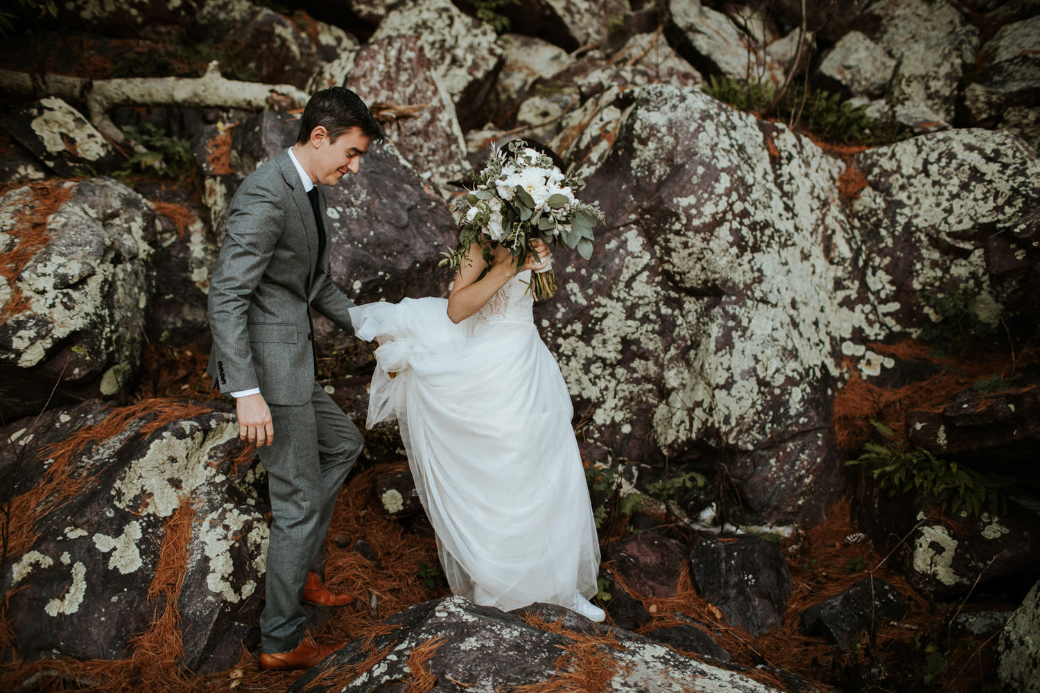 bride and groom walk among the boulders at devil's lake state park in Wisconsin