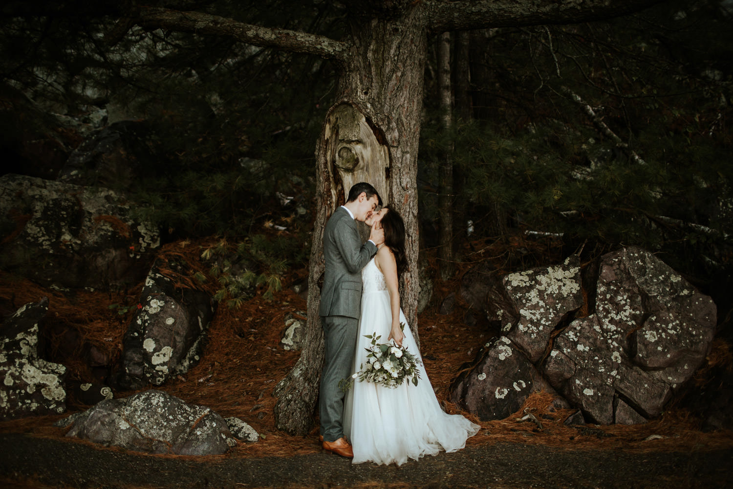 bride and groom kiss at devil's lake state park in Wisconsin. The wedding photographed by Mark Trela Photography