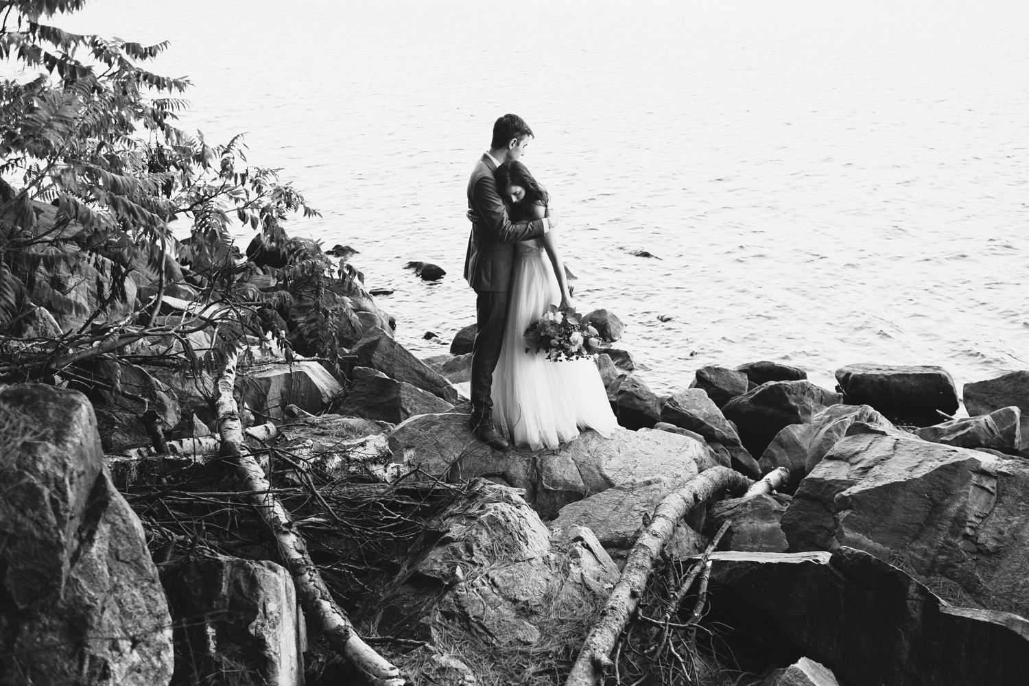 bride and groom embracing by the lake at the devil's lake state park