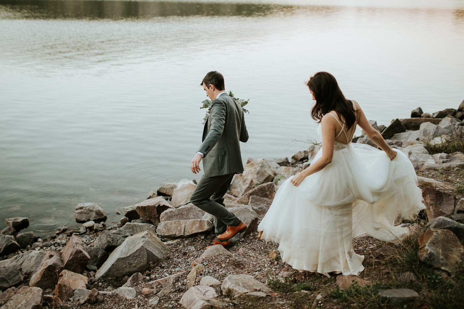 groom and bride walking by the lake at the devil's lake state park