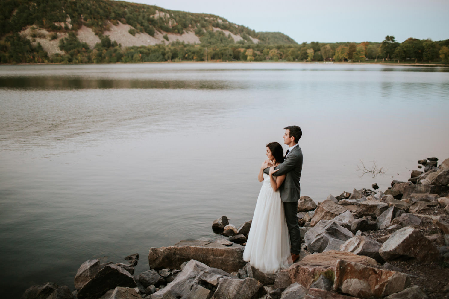 bride and groom watch the sunset at devil's lake state park in wisconsin