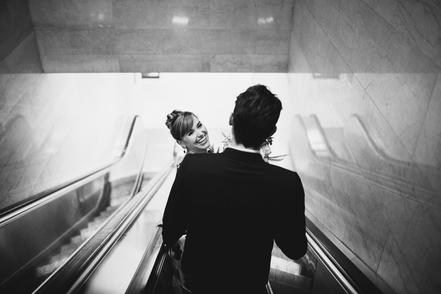 bride and groom ride down the escalator to the civil court house in Chicago