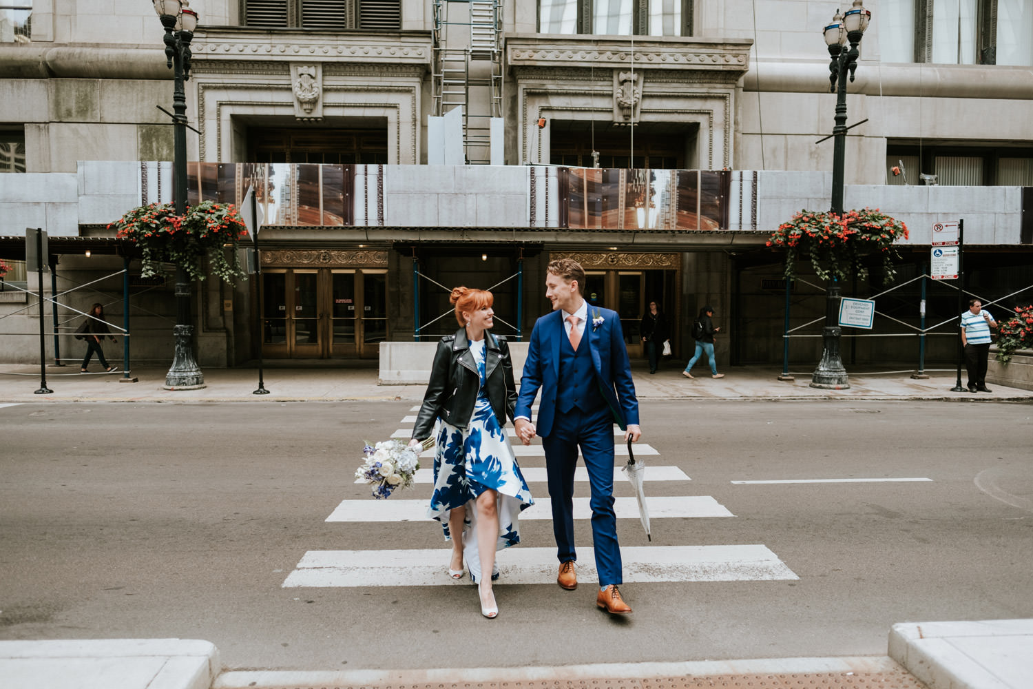 bride and groom cross a busy street in down town Chicago. Picture take during their October elopement