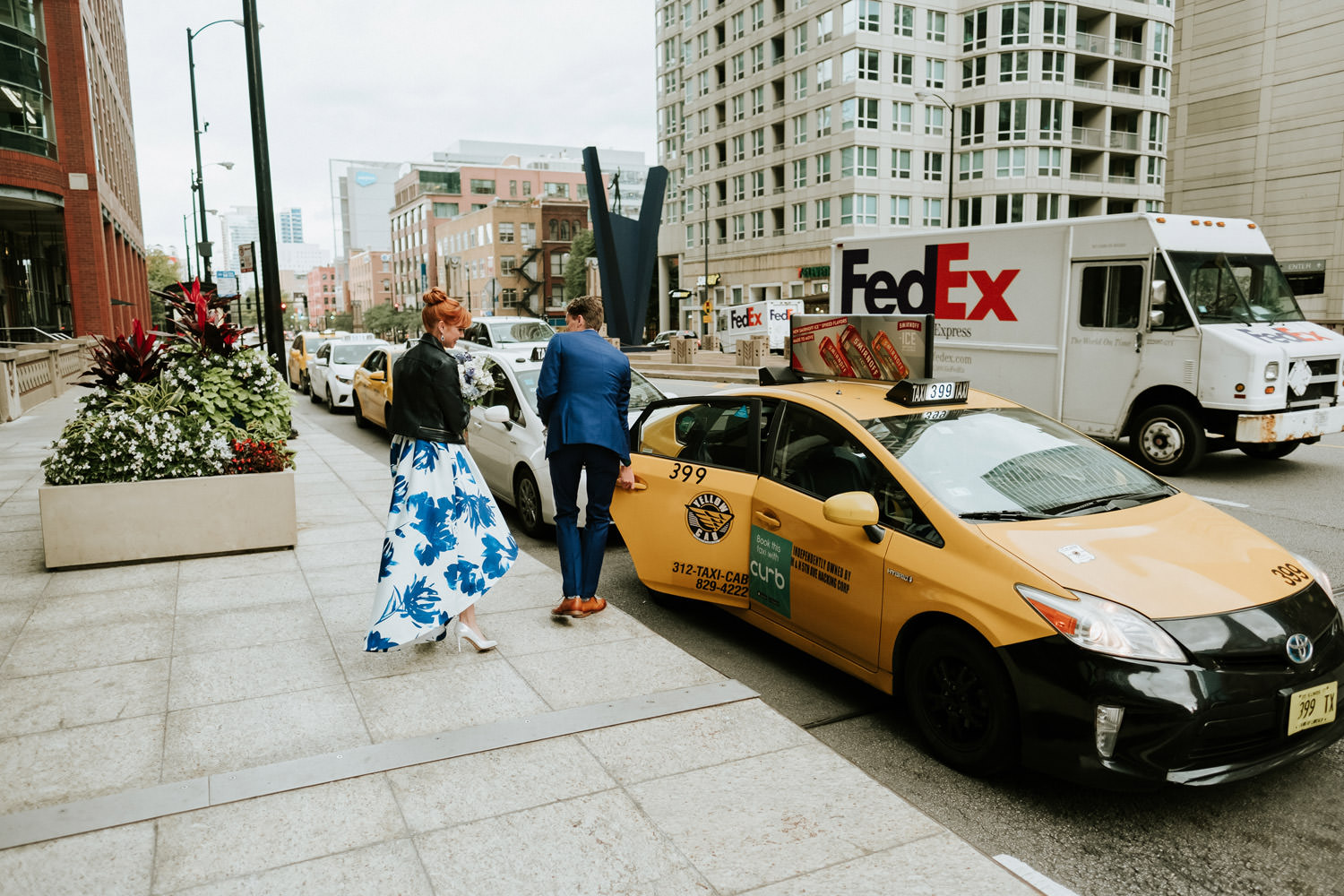 groom and bride take a taxi drive in downtown chicago during the wedding day