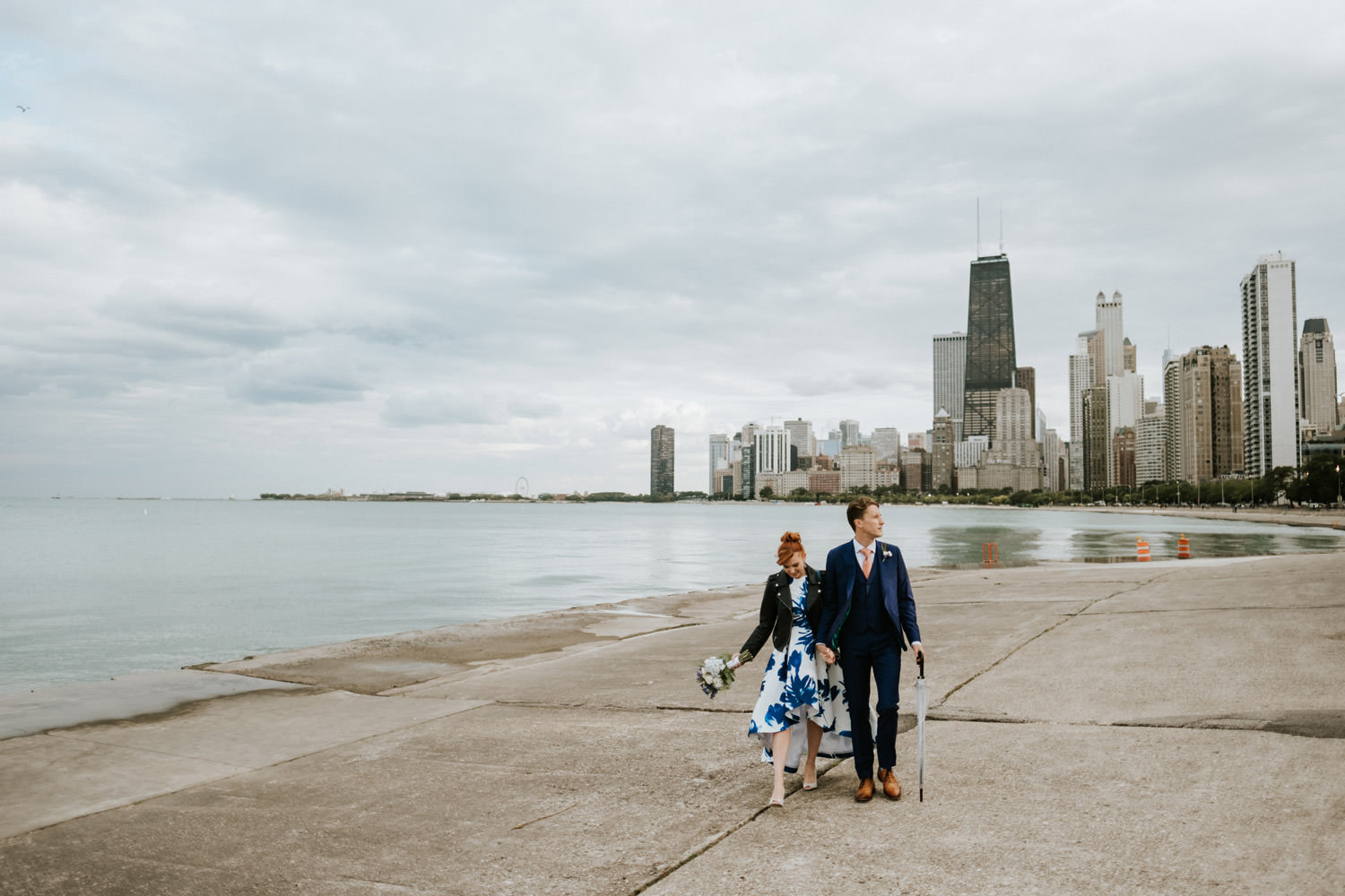 Bride and groom walk down the lake in Chicago during the elopement. The photograph shows Chicago skyline in the backdrop
