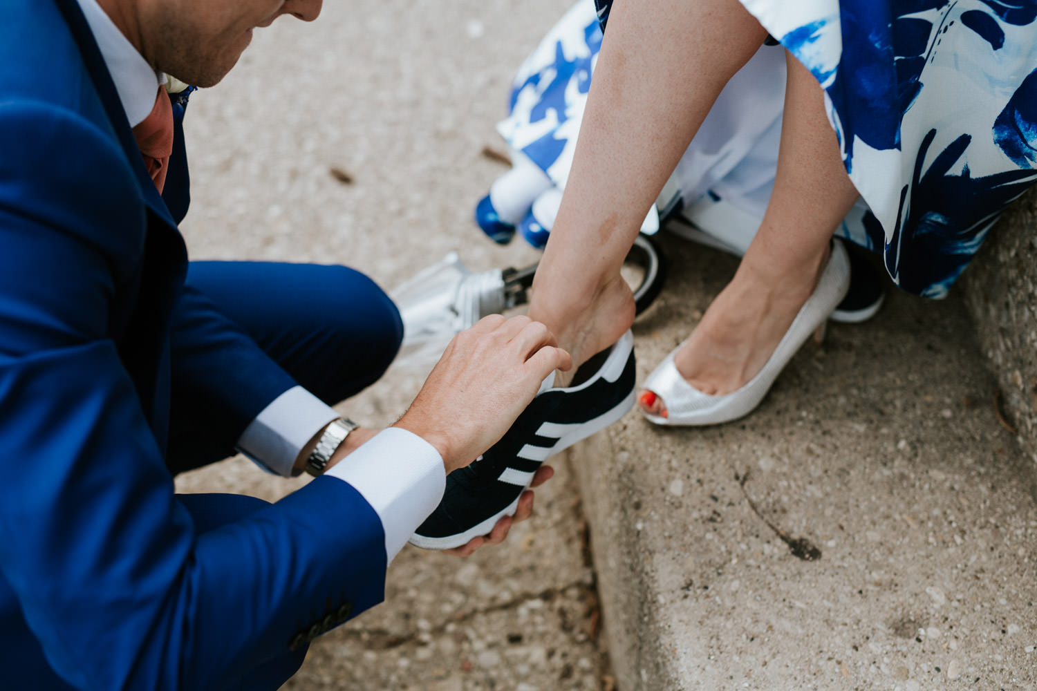 groom help her bride with changing the shoes during the wedding day