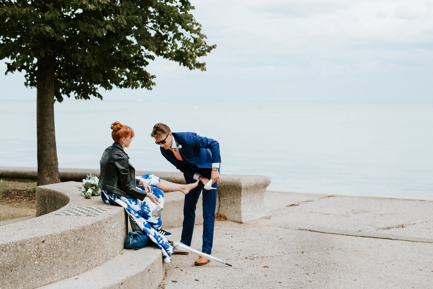 groom changes bride's shoes on their chicago elopement