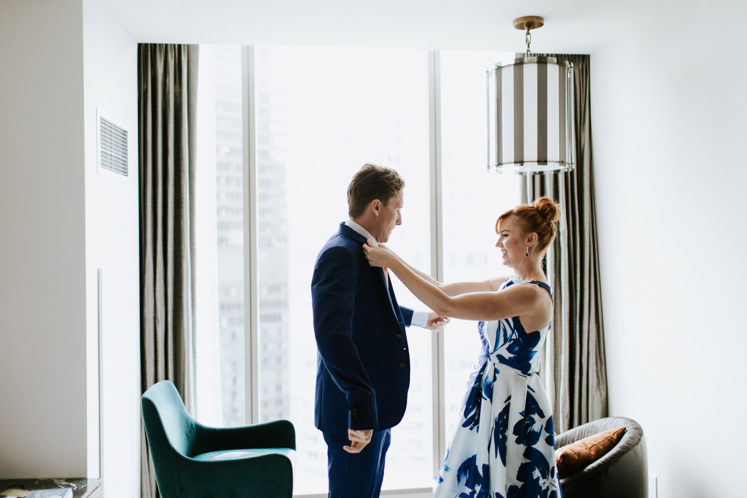 Bride help the groom with the suite while getting ready fore their elopement in Chicago