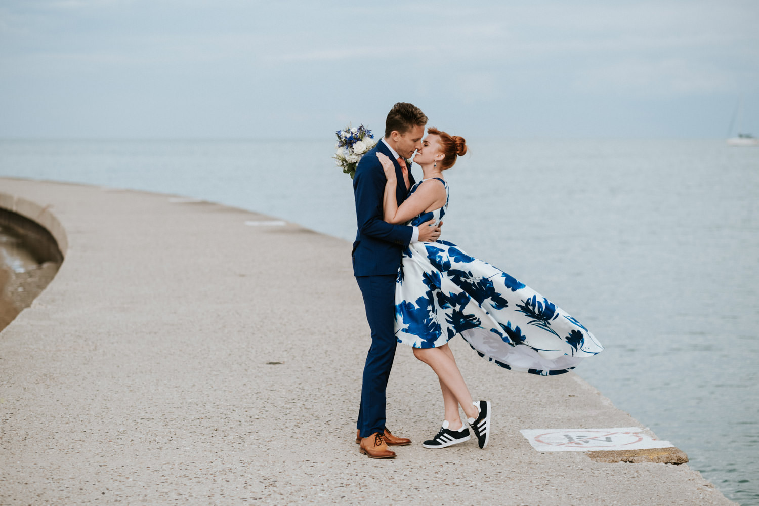 bride and groom kiss on north avenue beach in chicago during the their wedding / elopement day