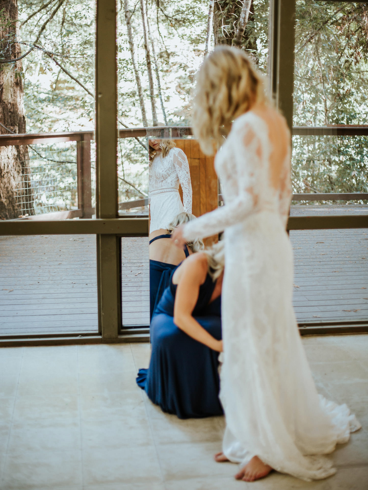 bridemaid helping the bride with the wedding dress at camp campbell wedding in California