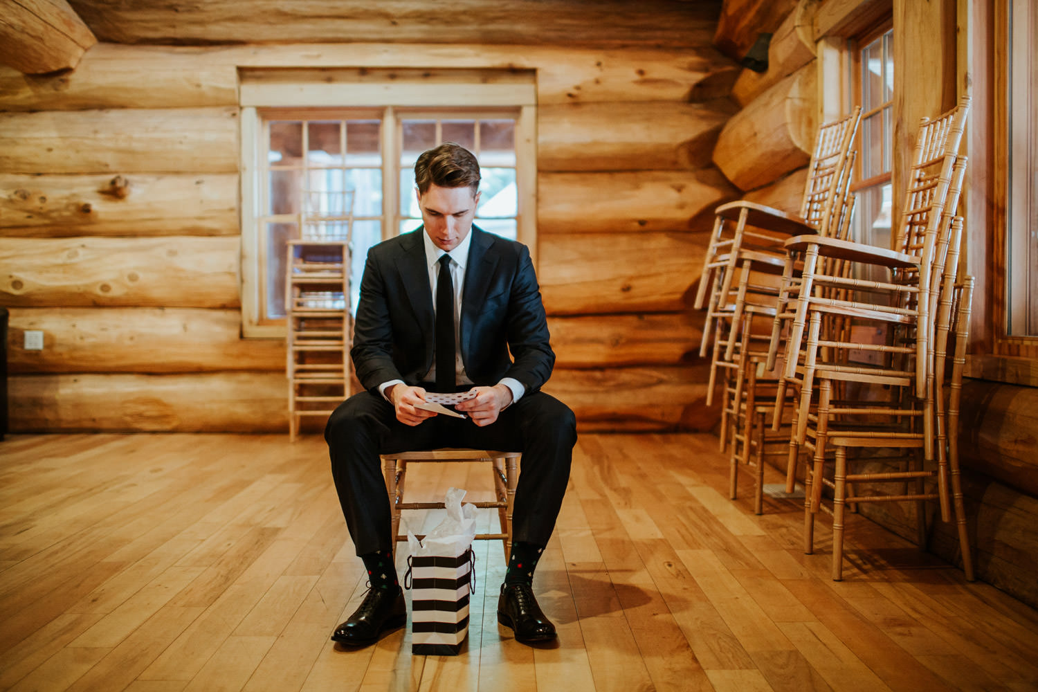 Groom sitting at Swanson Lodge at YMCA Camp Campbell while reading the letter form the bride