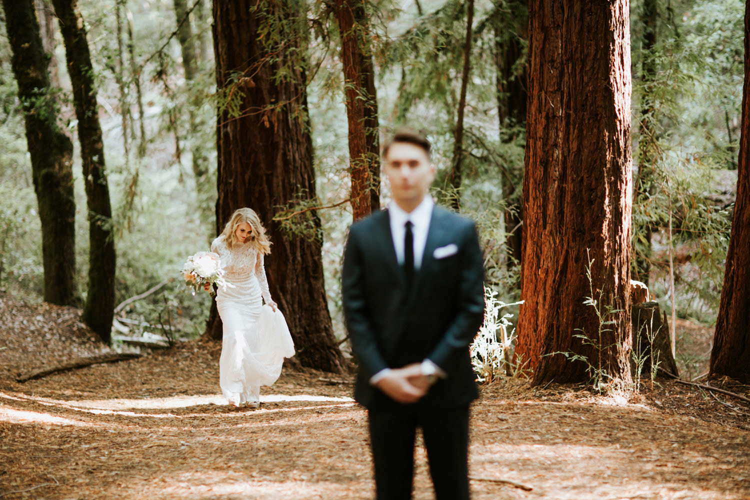 Bride walking behind the groom for the first look at YMCA Camp Campbell