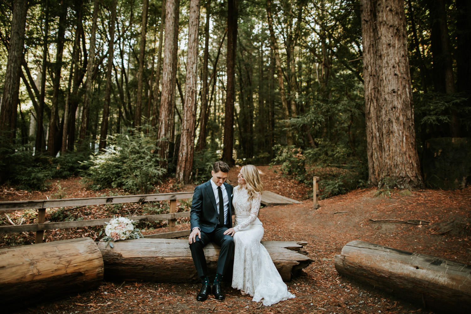 Bride and groom sit on a fallen Redwood during their wedding day at YMCA Camp Campbell