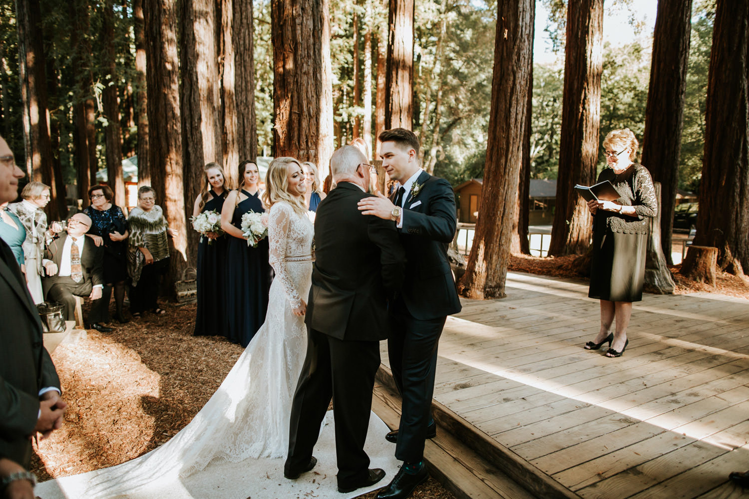 Groom embraces father of the bride during the wedding at YMCA Camp Campbell