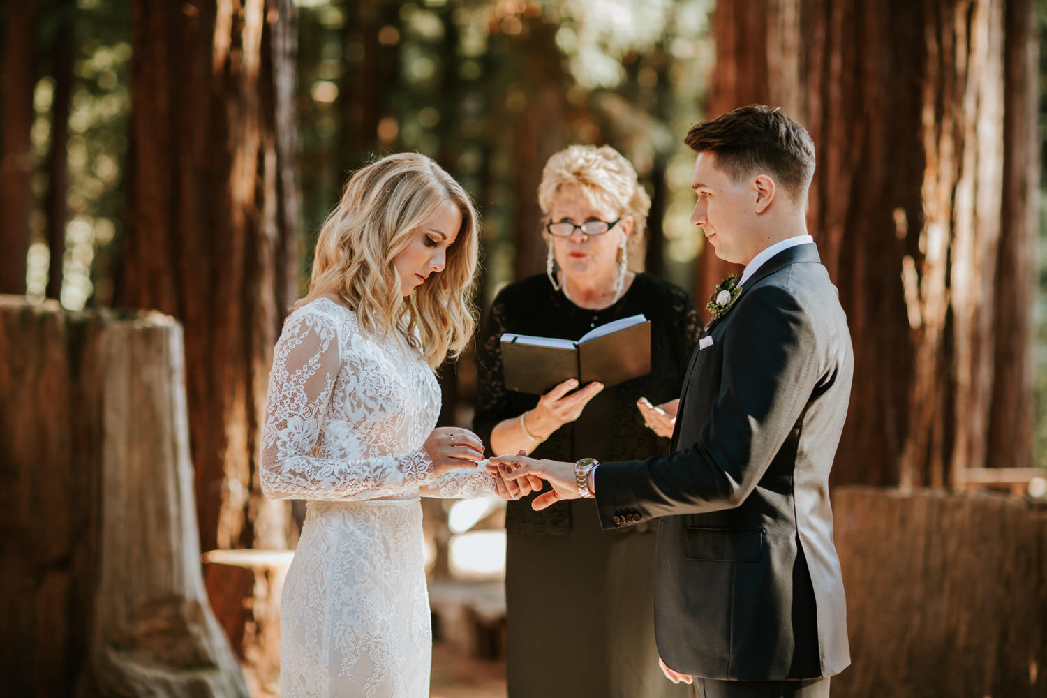Close up picture of the bride and groom exchanging rings during the wedding ceremony at YMCA Camp Campbell