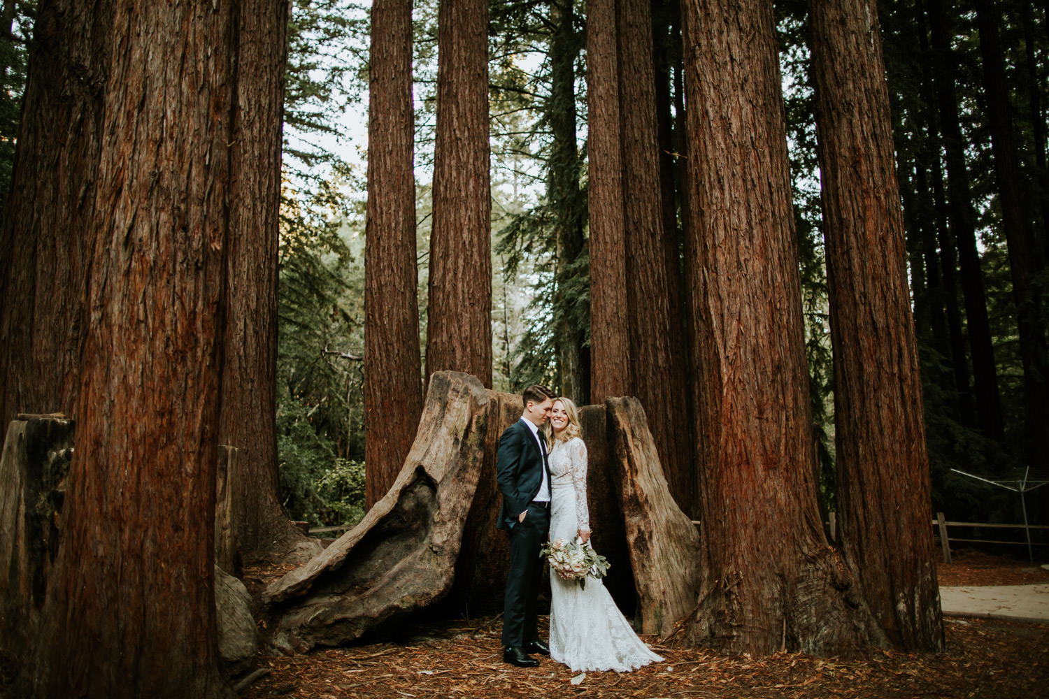 Bride and groom standing in front of redwood at YMCA Camp Campbell