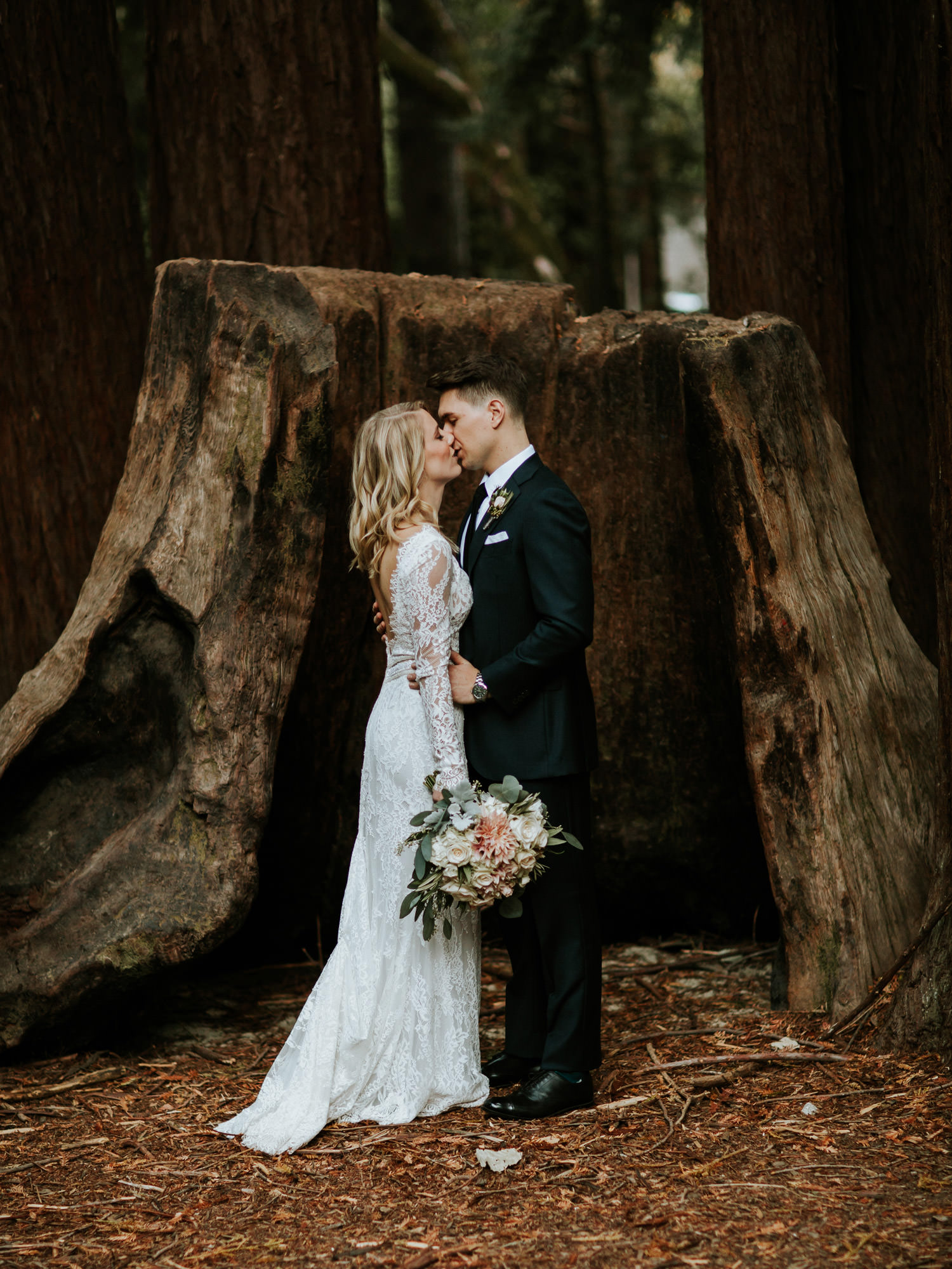 Bride and groom kissing in front of giant redwood stump at YMCA Camp Campbell