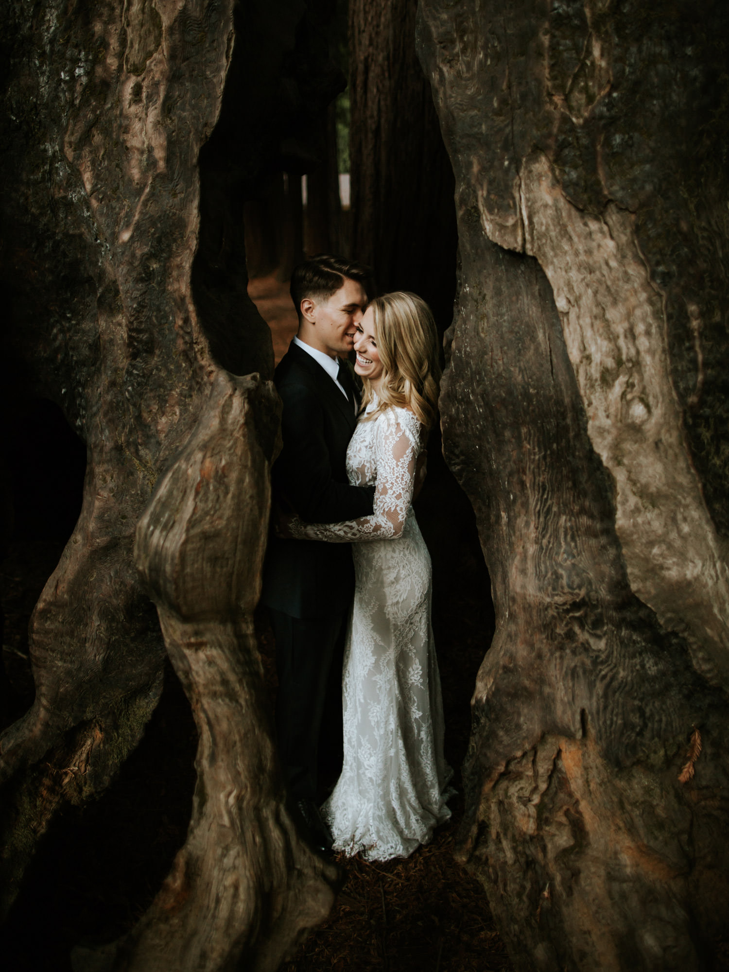 Portrait of the bride and groom take inside giant Redwood stump at Camp Campbell in California