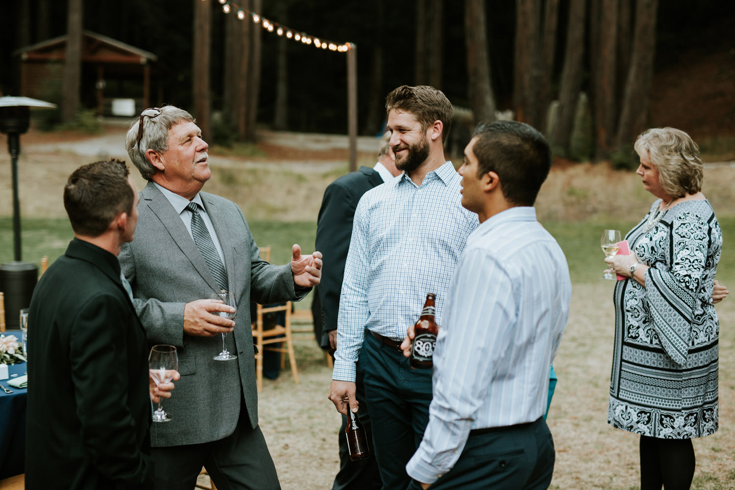 Wedding guest socialize during the wedding's cocktail hour at Camp Campbell in California