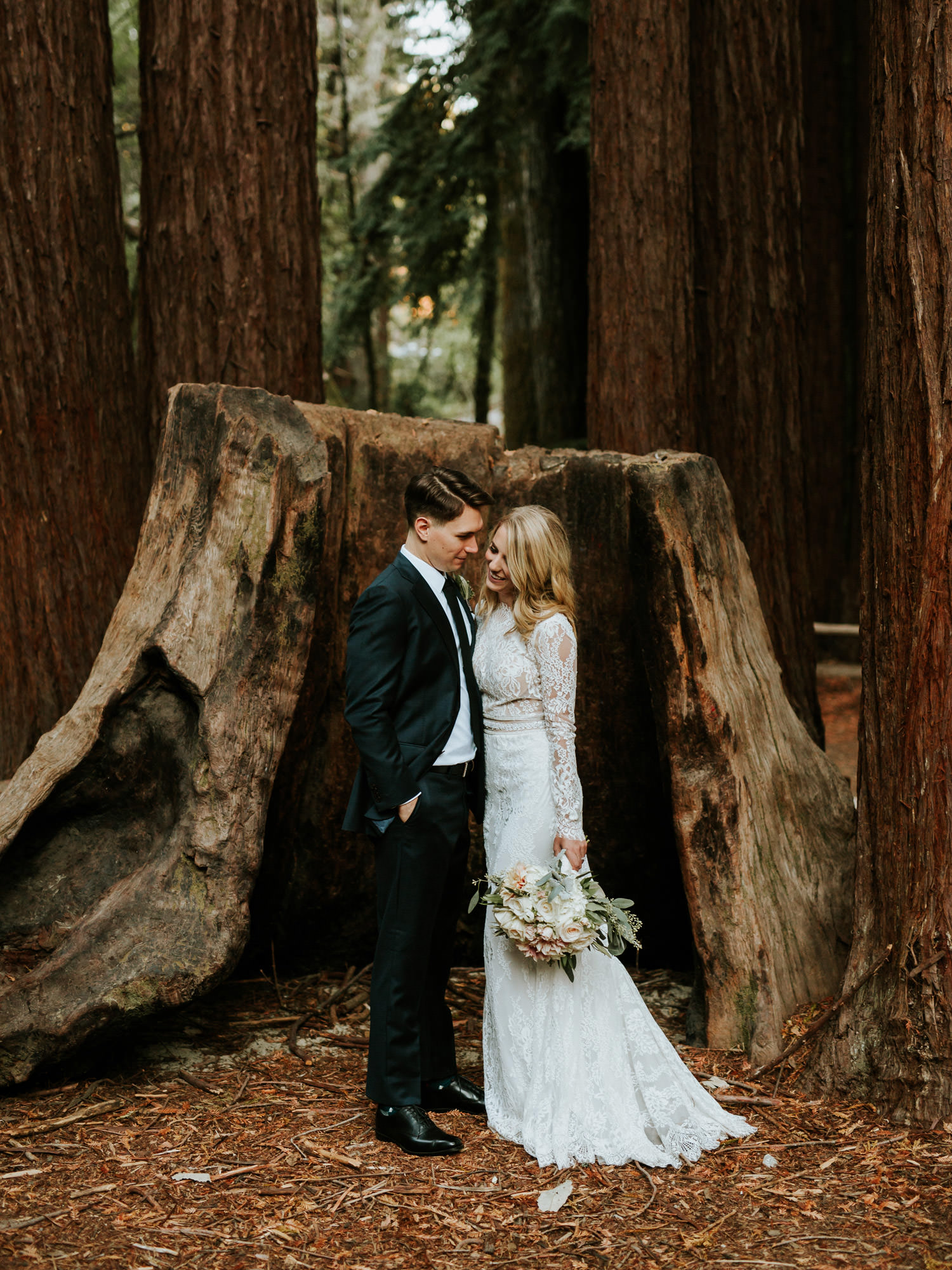 Portrait of the bride and groom taken in front of fallen redwood at YMCA Camp Campbell