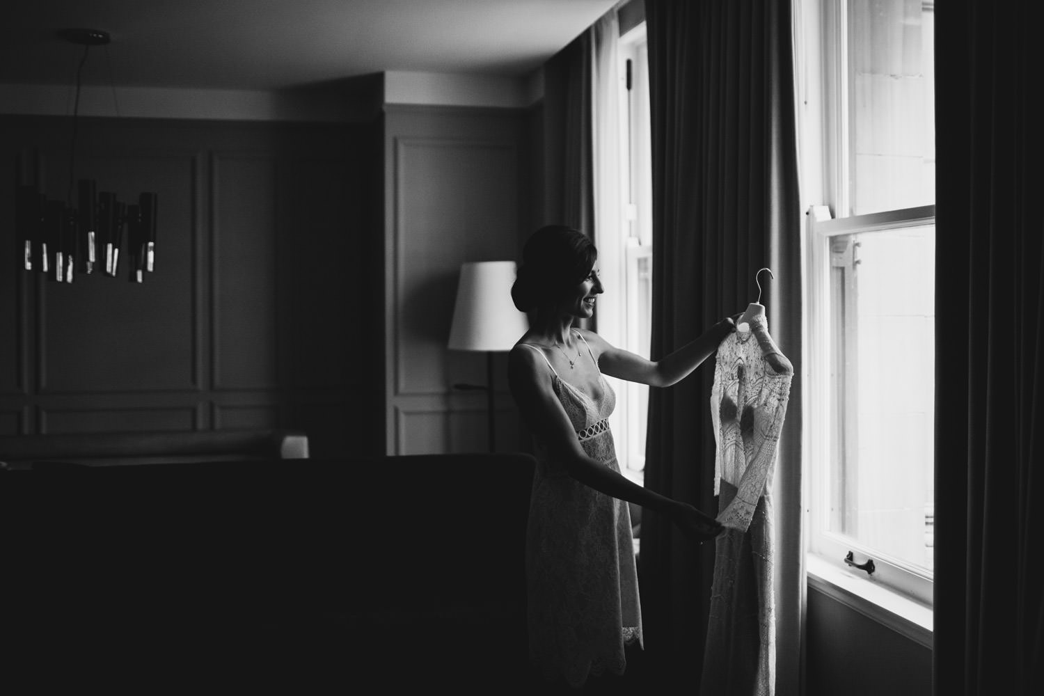 documentary wedding photographer captures the bride looking at her wedding dress before the first look