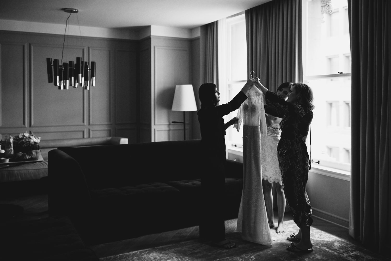 mother of the bride and maid of honor help the bride with the wedding dress photographed by a documentary wedding photographer in chicago