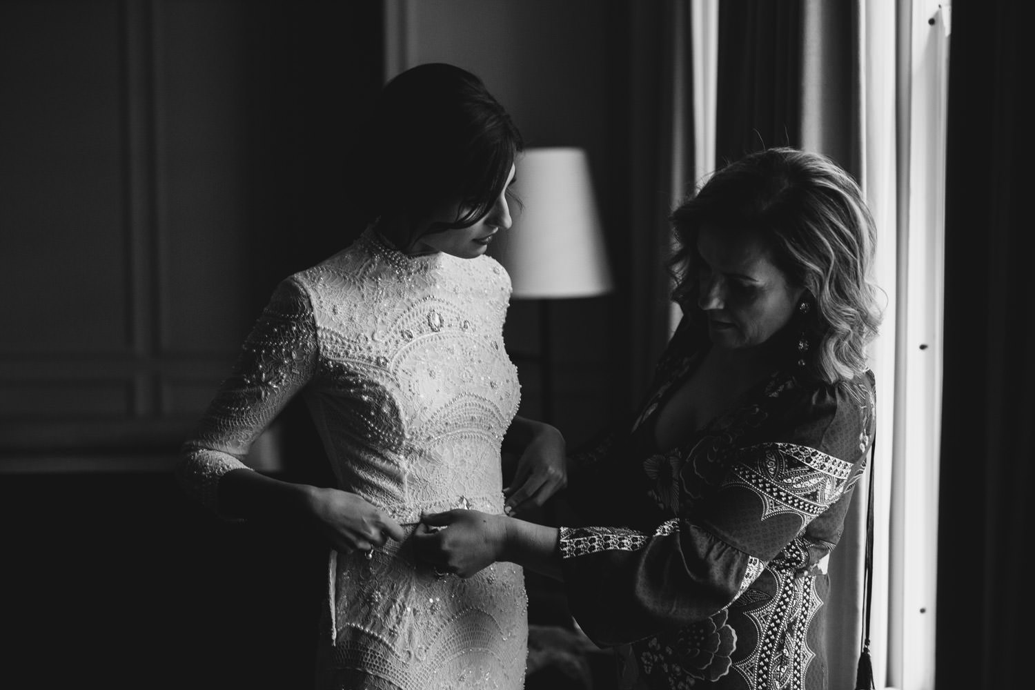 mother of the bride help the bride with the wedding dress