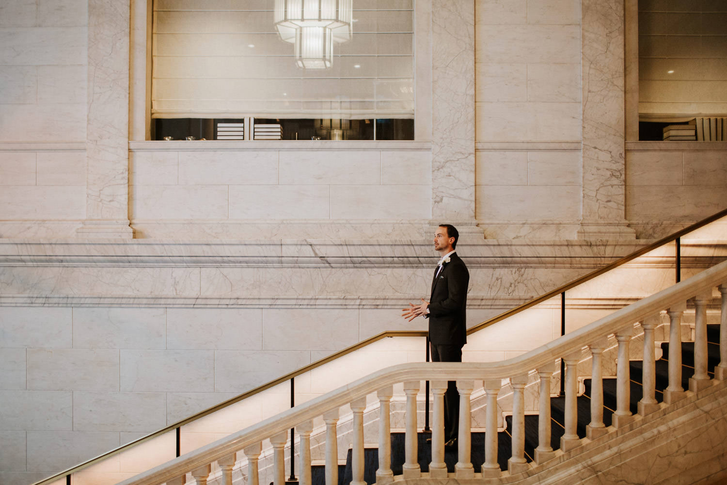 groom standing on the grand staircase of the gray hotel, awaiting to see his bride for the first time