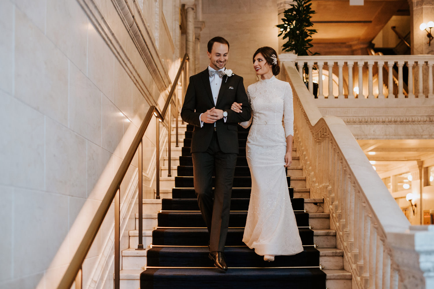 bride and groom walk down the grand staircase in the gray hotel