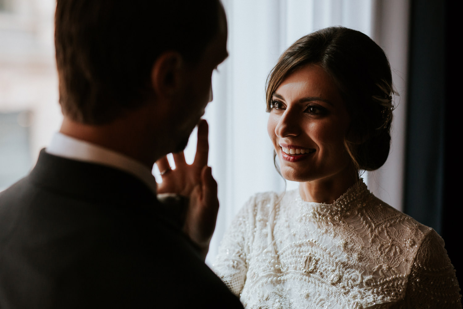 an photograph of the bride touching the face of the groom during the portrait session at the gray hotel