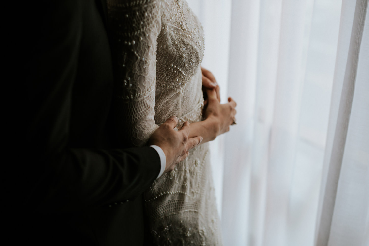 intimate moment of the groom embracing the bride before the wedding ceremony at the gray hotel