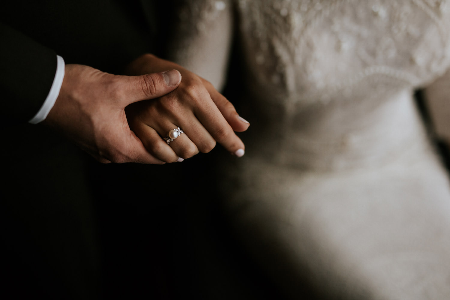 intimate photograph of the groom holding the brides hand during the wedding portrait session at the gray hotel