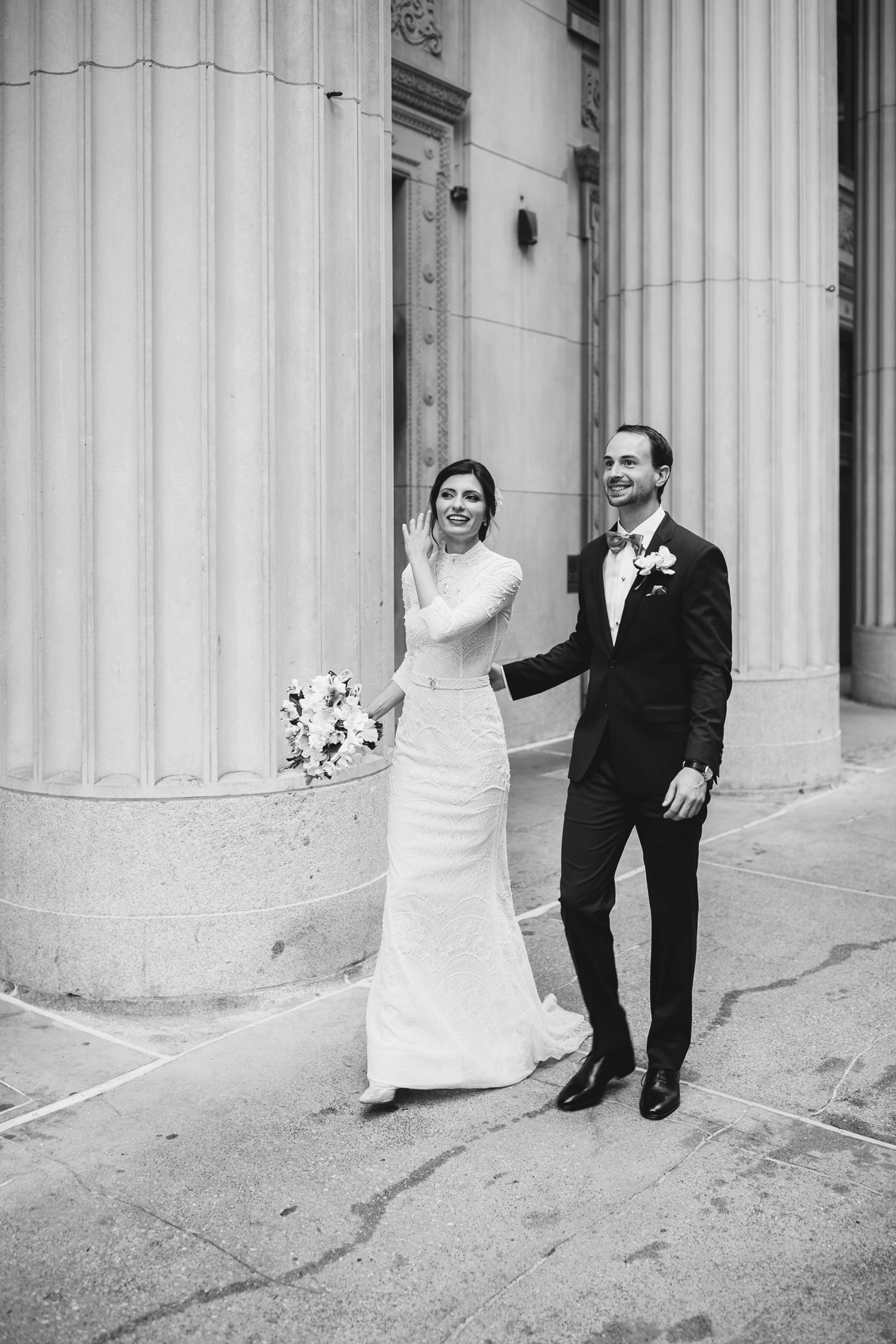 Bride and groom walk by Chicago board of trade in down town Chicago