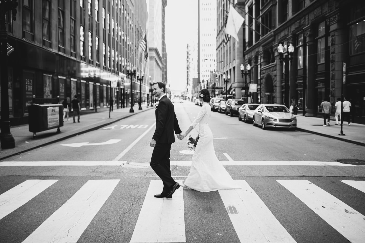 Bride and groom walk together down the street in Chicago downtown during their wedding day